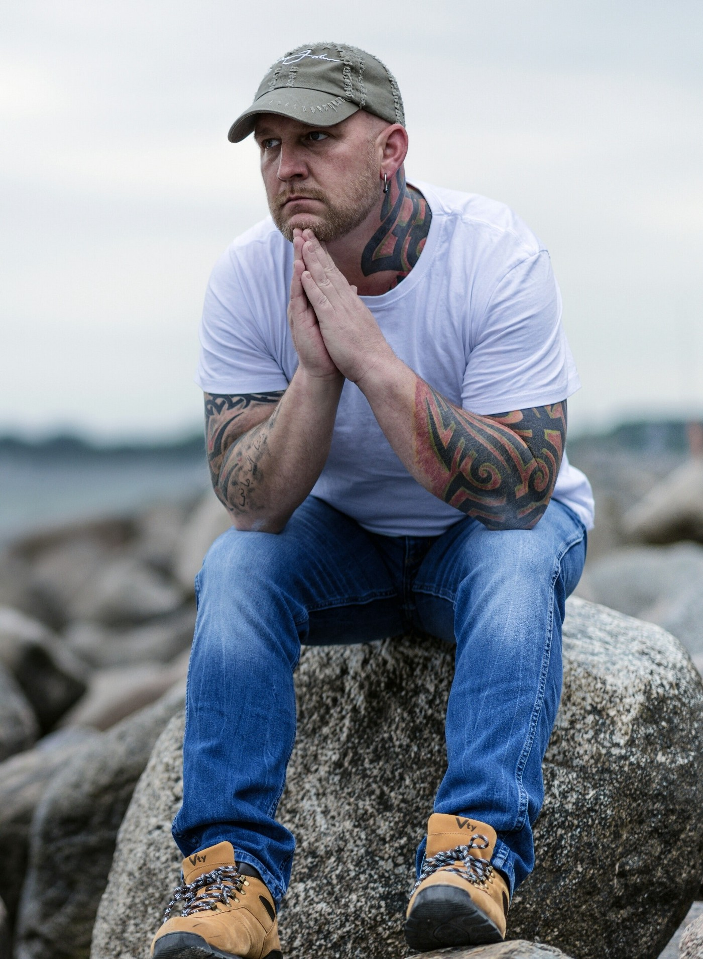 Man sitting outside on a rock looking lost in thought and a bit sad. Pensive. He is wearing a white t-shirt and jeans, with a green ballcap. His arms are tattooed. He has workboots on. The background is blurred but looks like a beach's rocky shore.