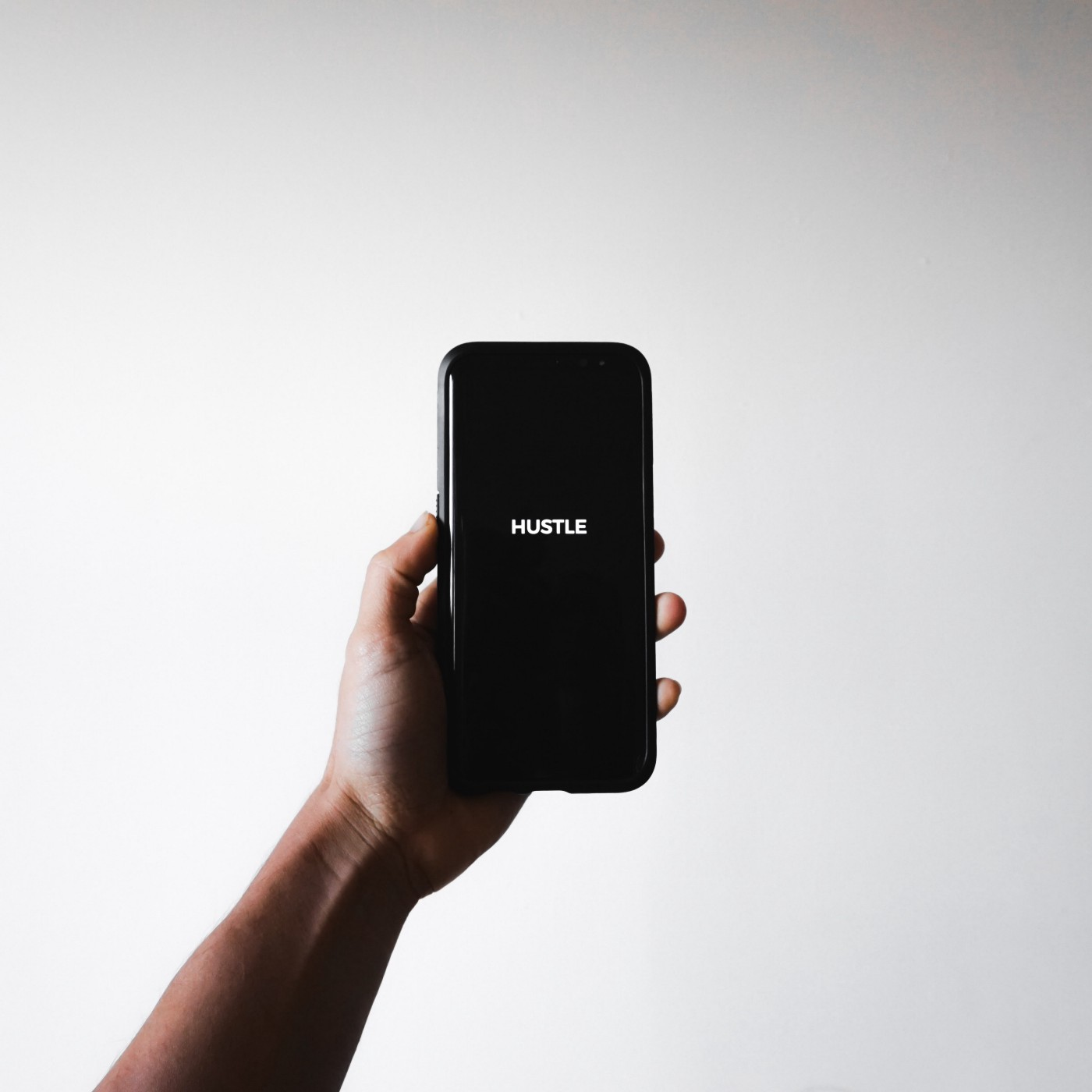 Smartphone displaying the word Hustle on a black screen.