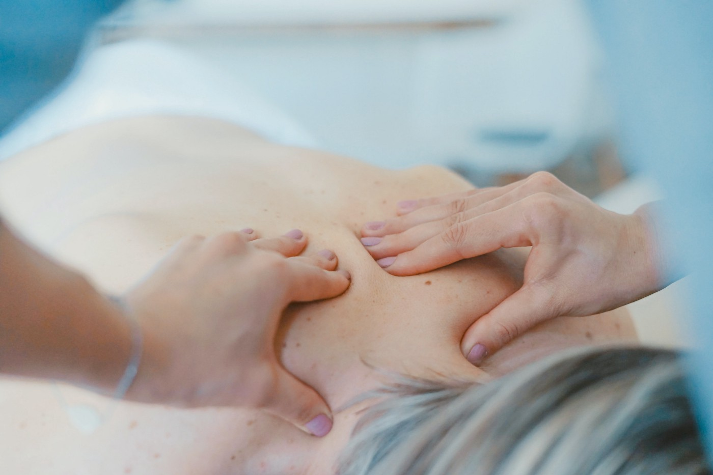 Picture of two hands massaging someone's back