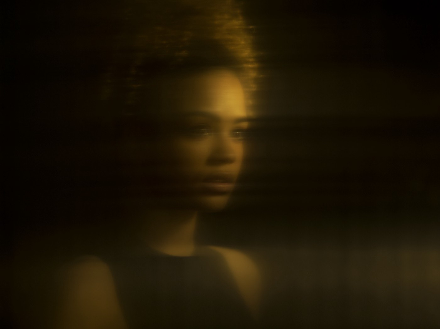 Distorted gold-tinted reflection of a young Black woman.