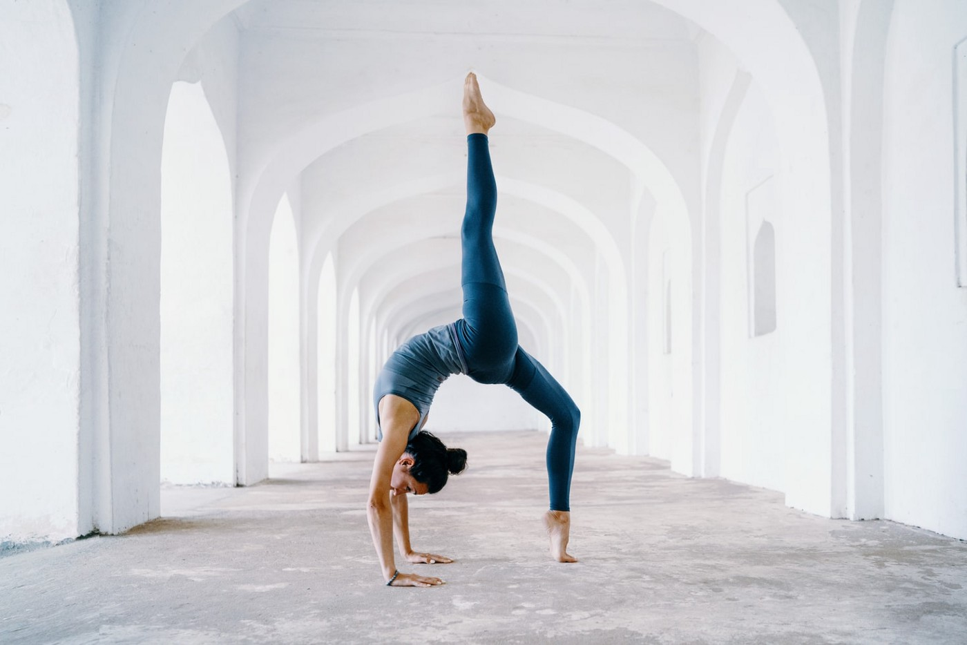 A woman does a challenging inverted yogi pose in a simple white hallway outdoors. The sun shines through several doorway openings on the left.