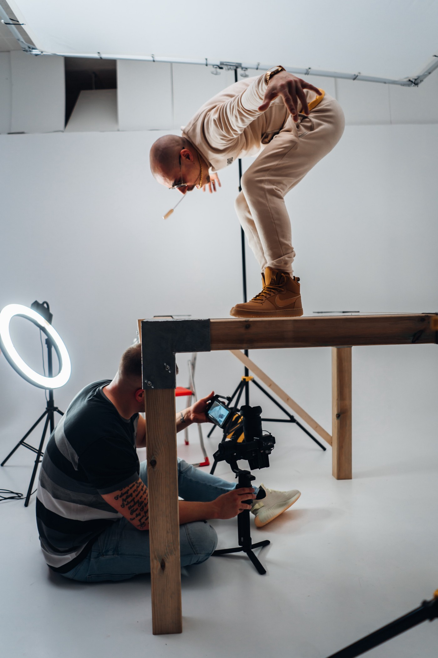 Photoshoot with the photographer sitting under a table while his subject poses on top of it.