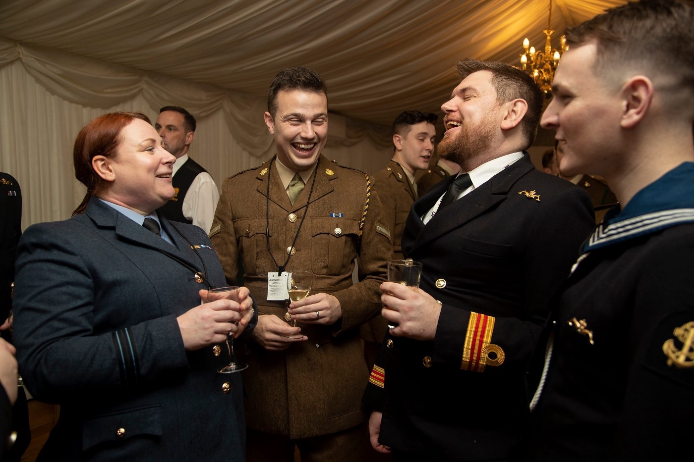L-R: A woman from the RAF, a man from the Army, and two men from the Navy laugh in a marquee