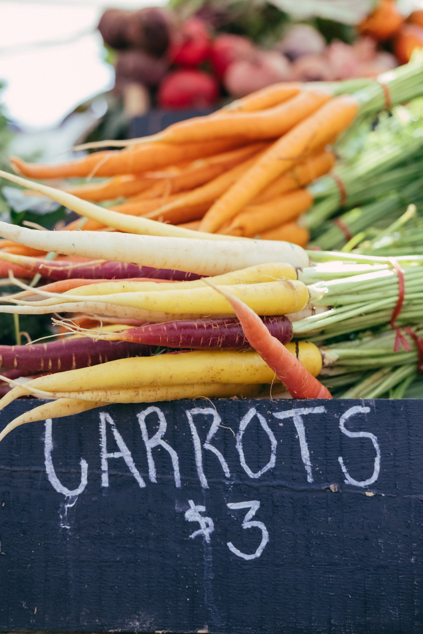 Fresh carrots for sale at Farmer's market. Bunches of carrots for sale.