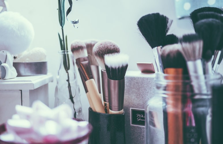 A close up camera shot of a variety of beauty products like brushes, cotton balls, and q-tips