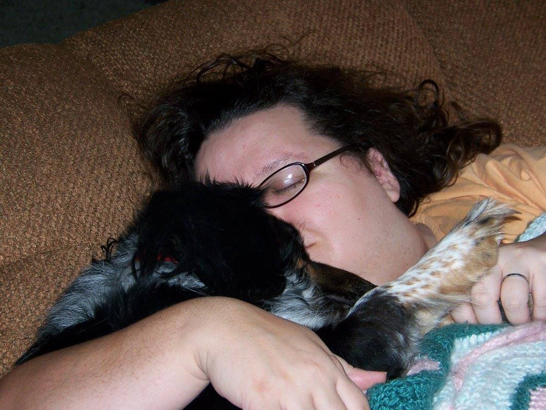 Author snuggling her dog Flash. Both have their eyes closed.