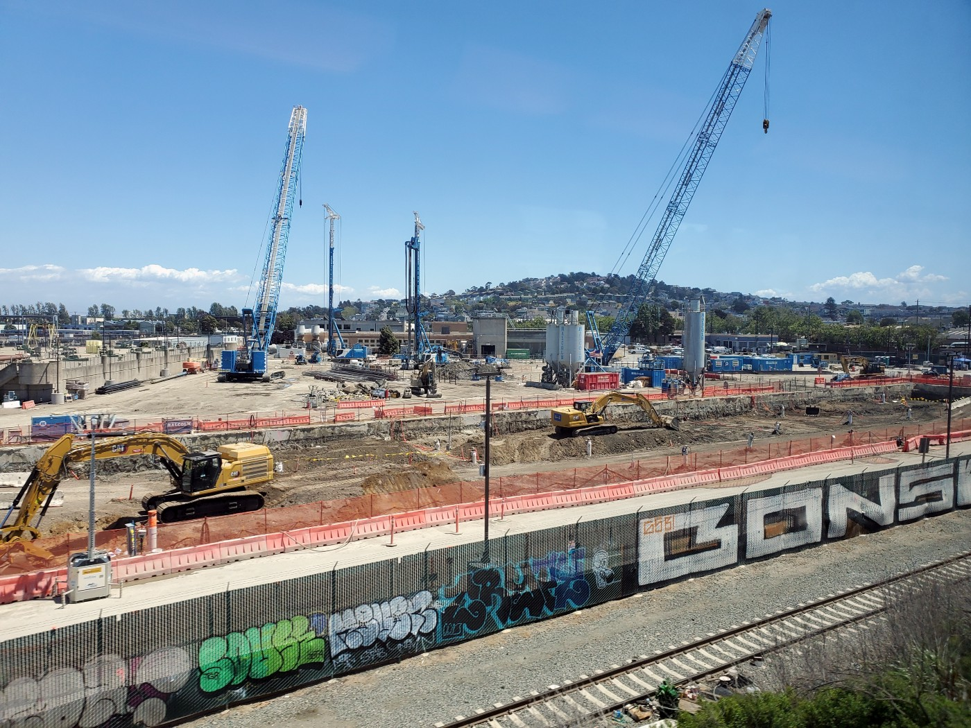 Two blue cranes and two other construction vehicles continue work at the worksite for The Walsh Group Ltd. against a bright blue sky while workers focus on concrete compressive strength monitoring..