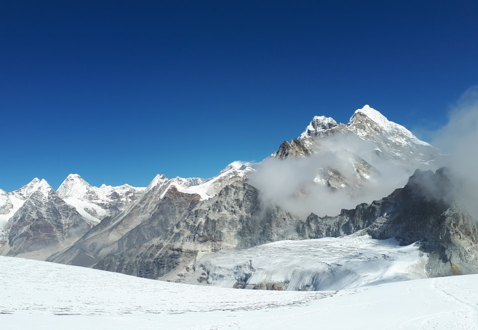 In the foreground is the snow laden floor of a glacier with some footprints in the snow. In the distance is a line of snow capped mountain tops.