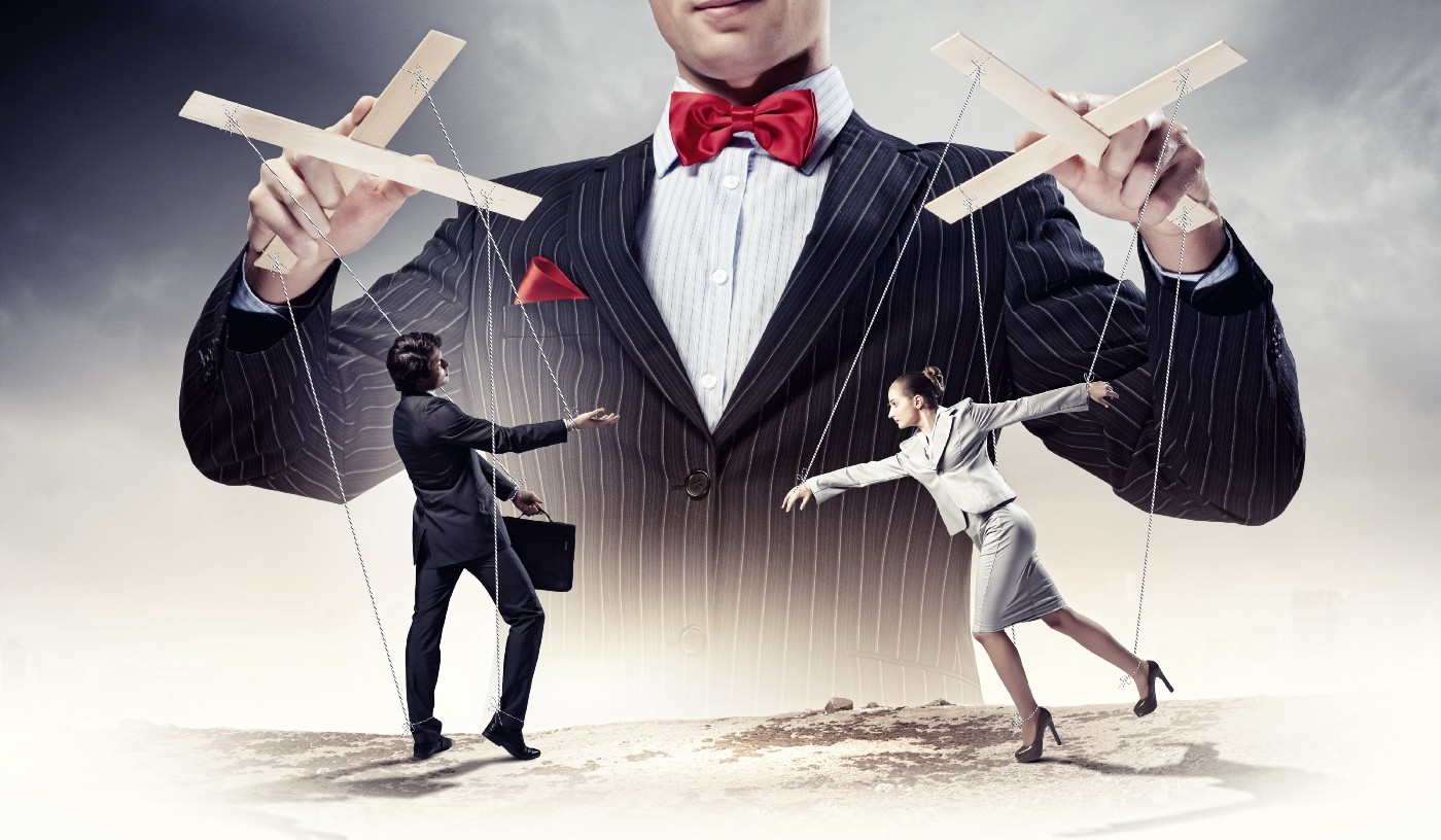 A business woman and man being controlled by marionette strings.