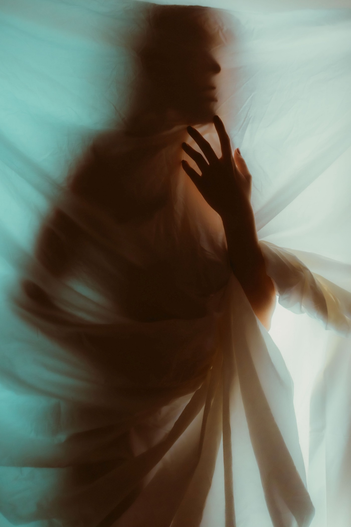A pale ghost-like figure—of unidentified gender—enshrouded in a transparent fabric, a gauzy curtain like a scrim used in theater productions. The figure's face is not visible. Its body is hidden, wrapped up, almost trapped and entangled in this thin film-like curtain; only its rather large left hand is out and it is bent at the elbow, hand up almost in a dance movement or supplication, palm facing inward, index finger lightly touching chin.