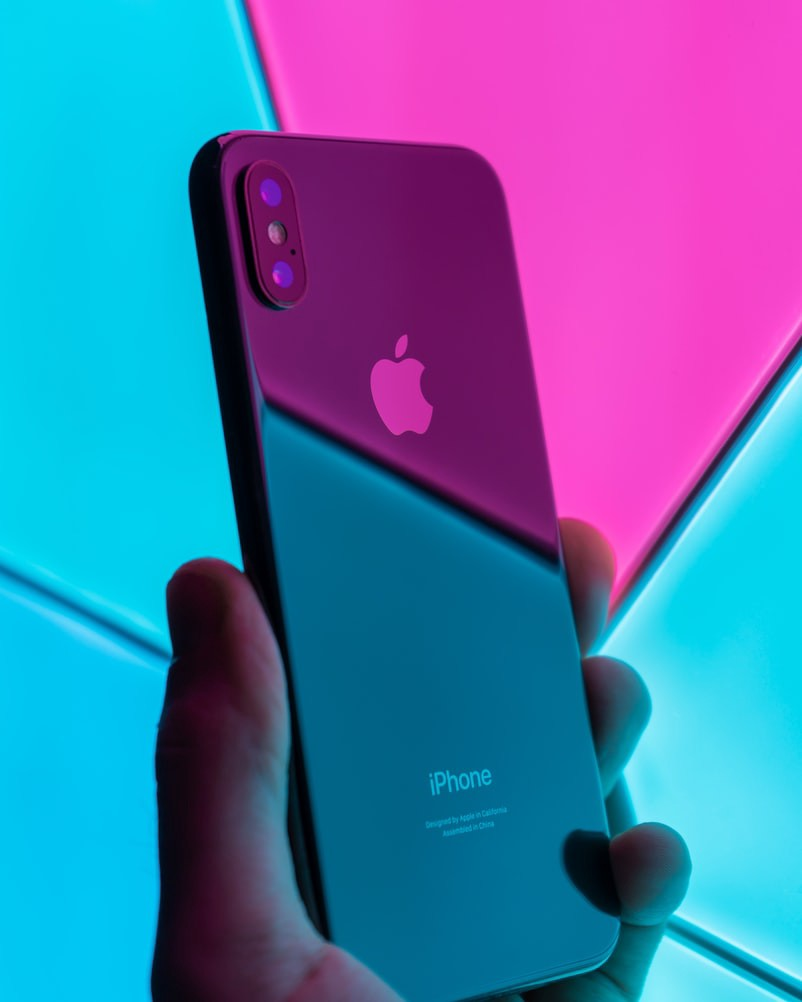 Photo of someone holding an iPhone against a neon background, taken by Daniel Korpai on Unsplash.