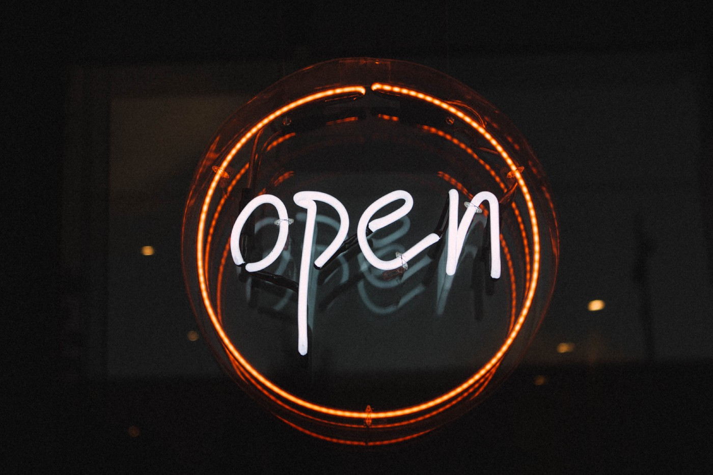 "Neon ""open"" sign with white text, surrounded by orange ring, on a black background. Image has dim reflection."