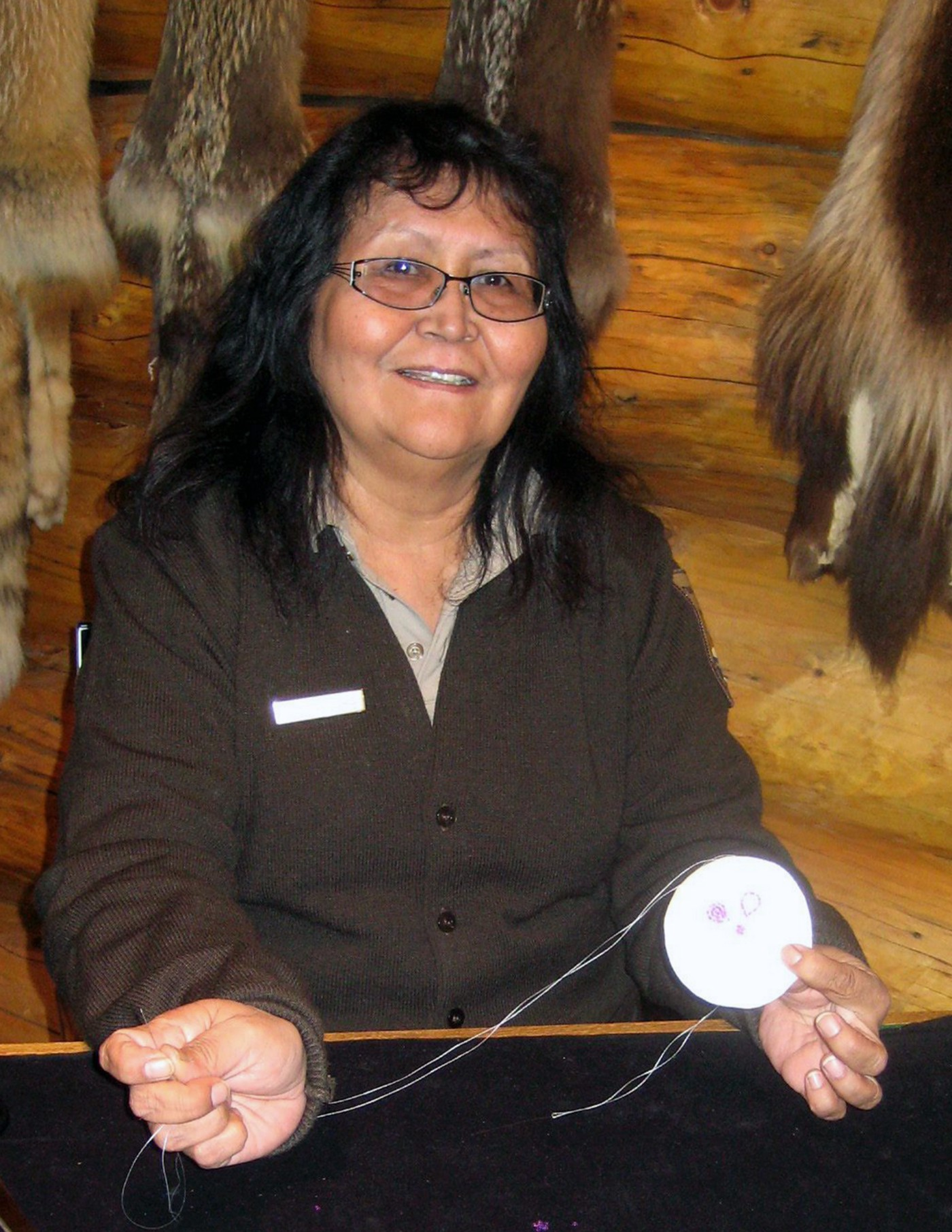 Sylvia in uniform inside the visitor center doing traditional crafts