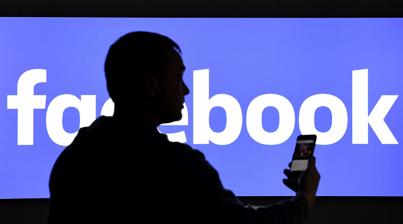 A man with a smartphone stands in front of a monitor with the Facebook logo.