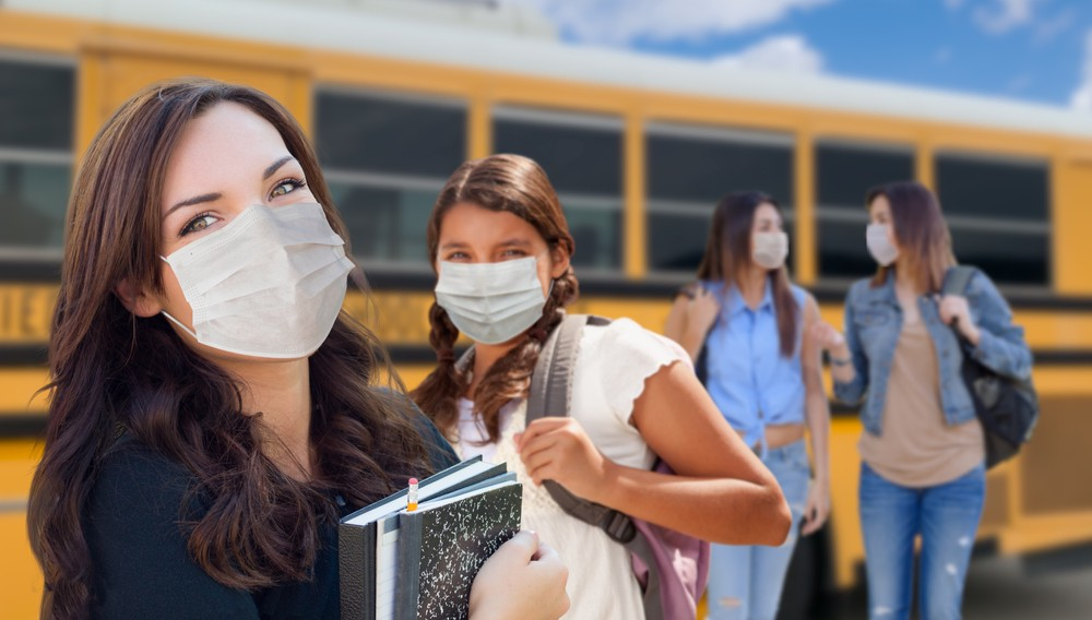 Four high school girls wearing masks are standing in front of a school bus.