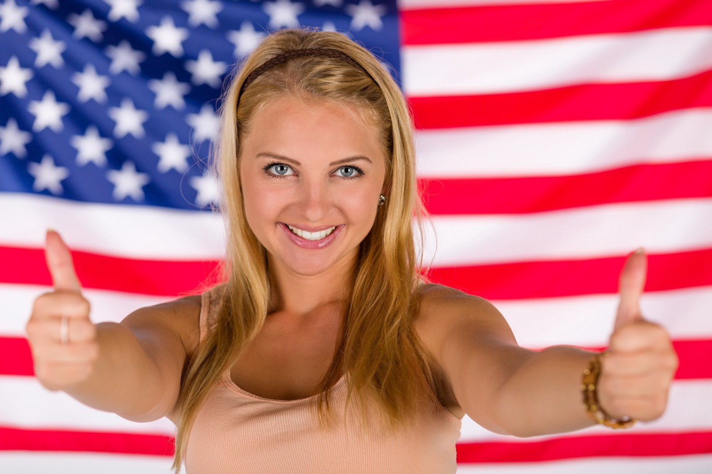 A smiling blonde-haired, blue-eyed white woman gives us two thumbs us while standing in front of an American flag.