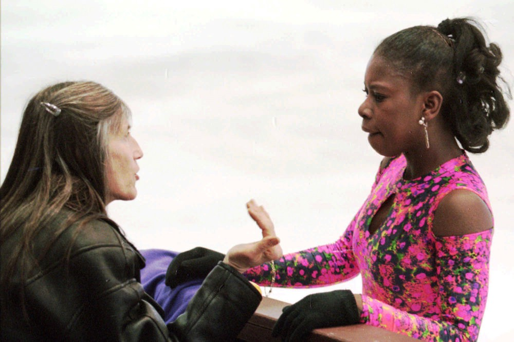 Surya Bonaly of France, receives instructions from her mother and coach Suzanne Bonaly, left, during a practice session