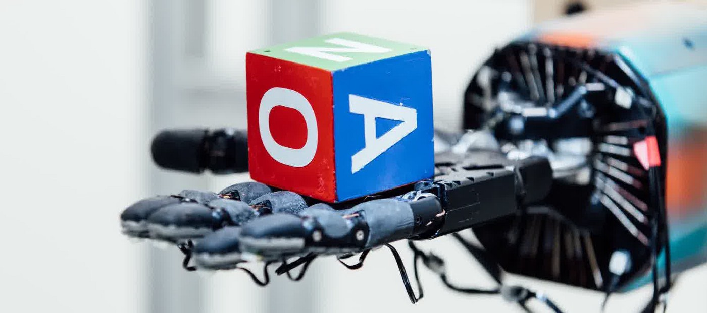 robot hand holding dice with letters on it
