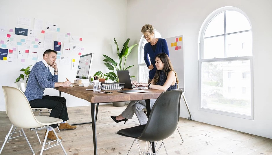 Three people sitting and working in office