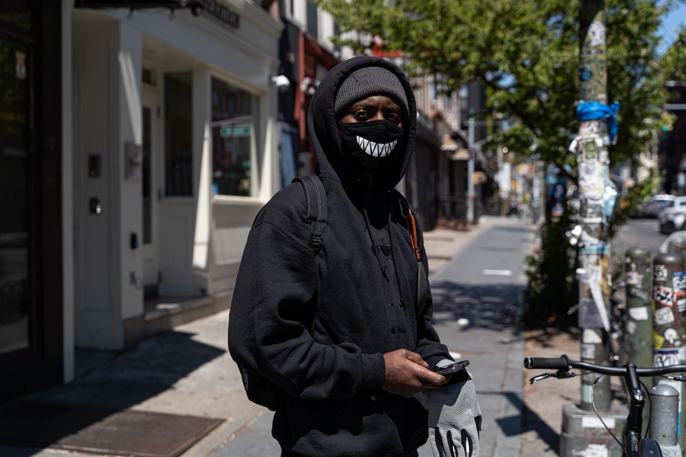 A black man poses for the photo wearing a dark hoodie, black face mask, beanie.
