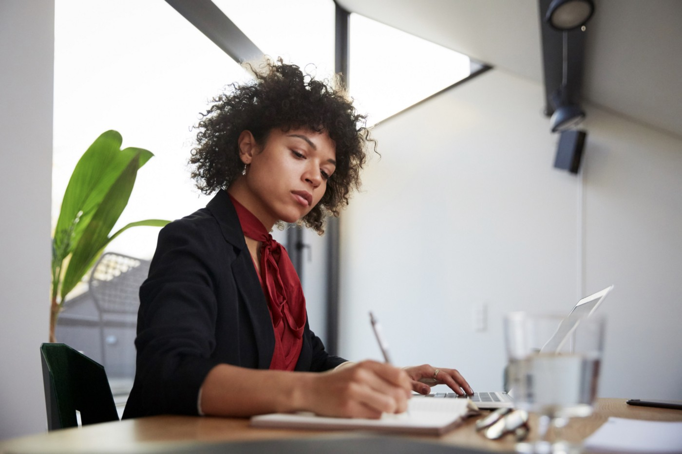 Confident Black woman writing down invoice at her computer.