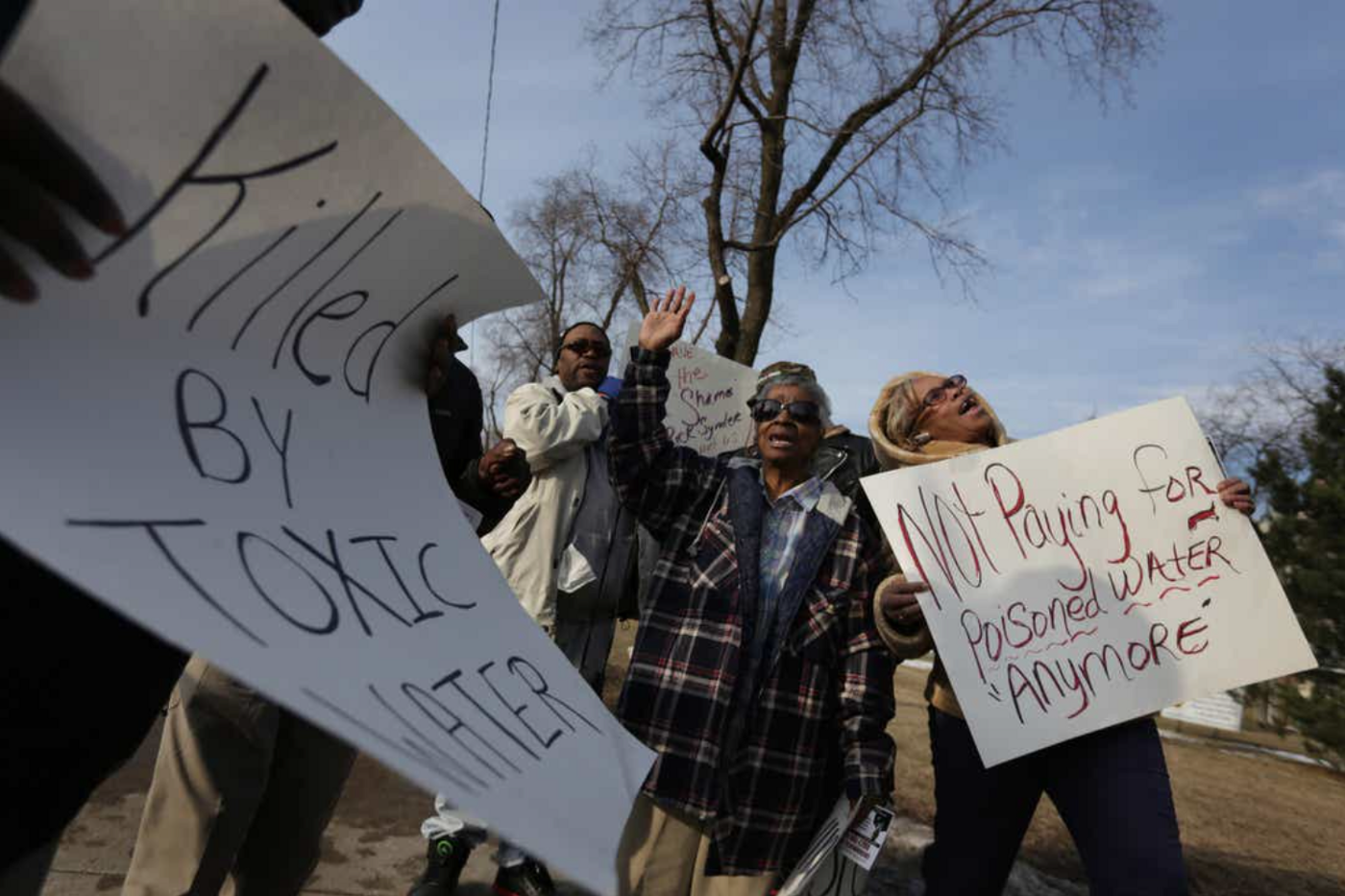 """Protesters in Flint, Michigan holding signs that read: """"Killed by toxic water"""" and """"Not paying for poisoned water anymore"""""""