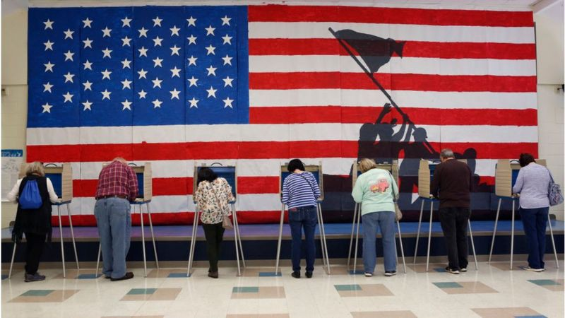 Against backdrop of U.S. flag and silhouette of Iwo Jima Memorial, line of voters cast their votes on machines.