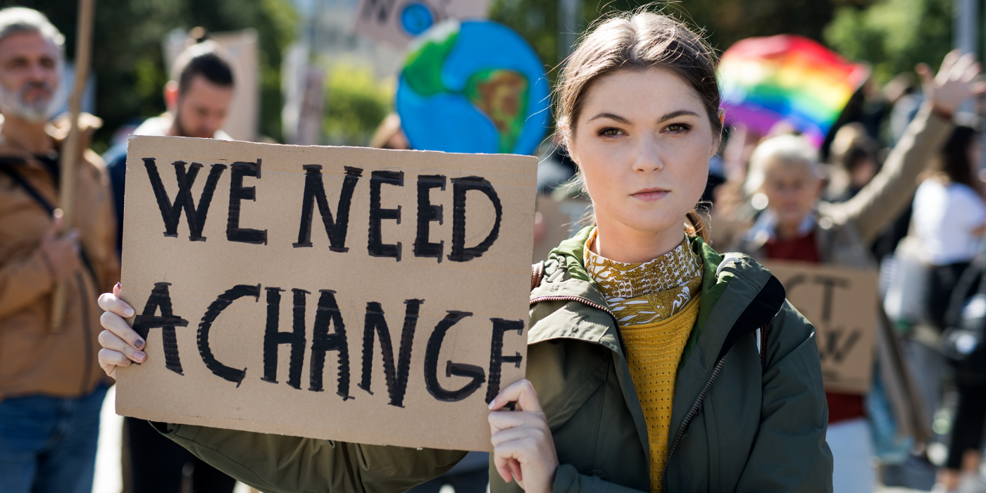 "A protestor at a climate change protest holding a sign that says ""WE NEED A CHANGE"""