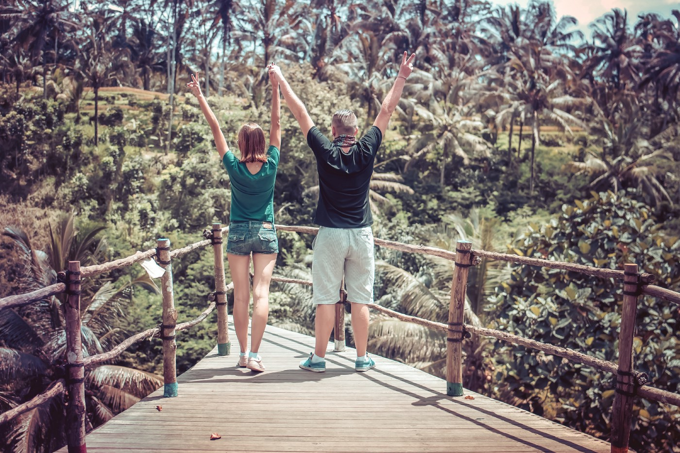 Two people hold their arms up in celebration on a bridge and forest setting