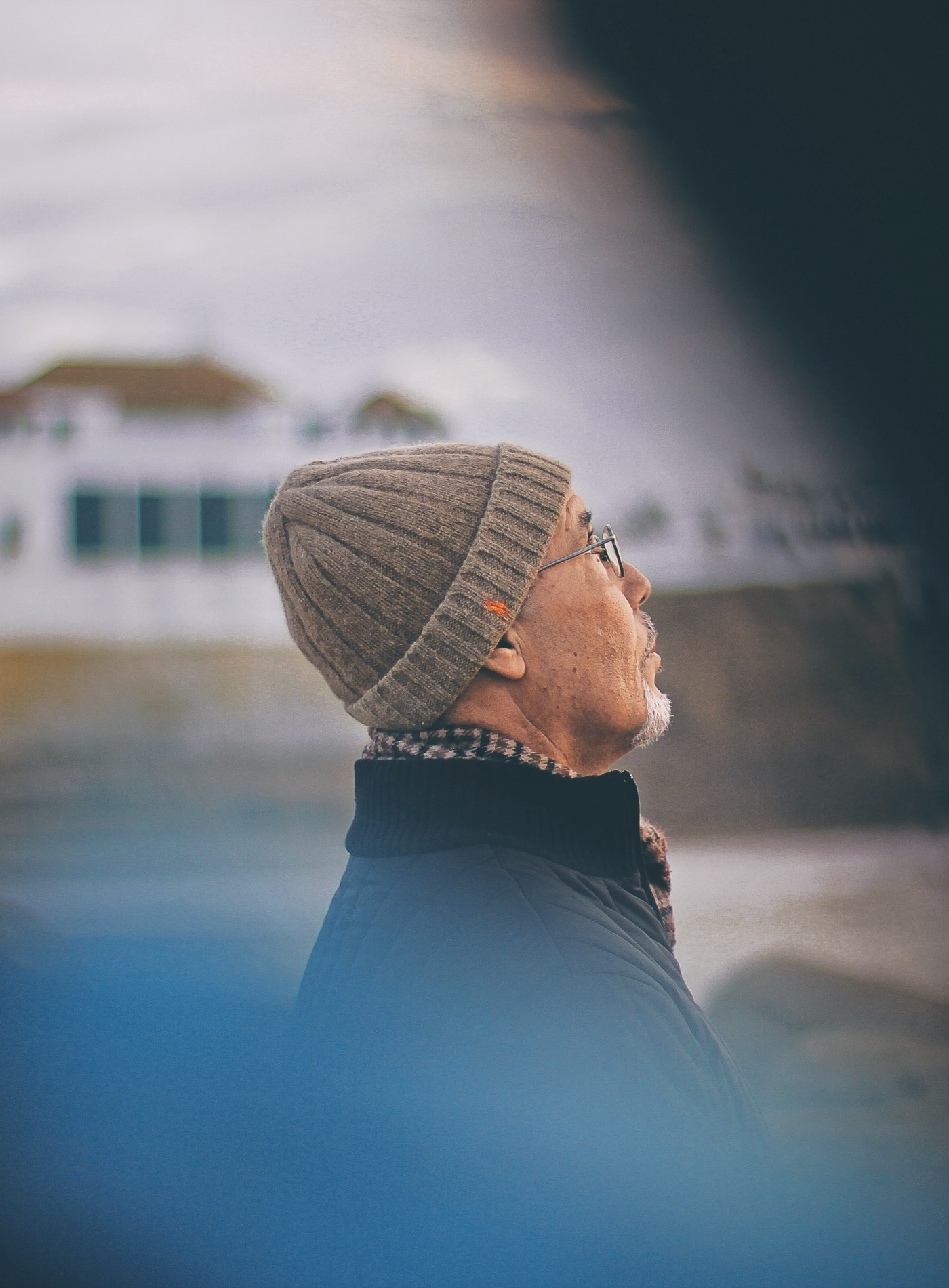 An older gentleman in glasses with scarf, coat, and stocking cap, outside looking up into the sky.
