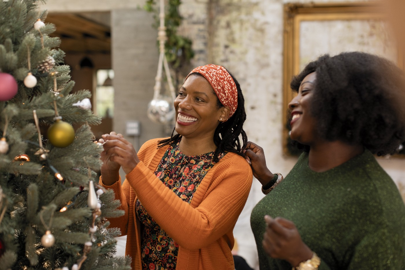 Two Black woman decorating the Christmas tree with smiles.