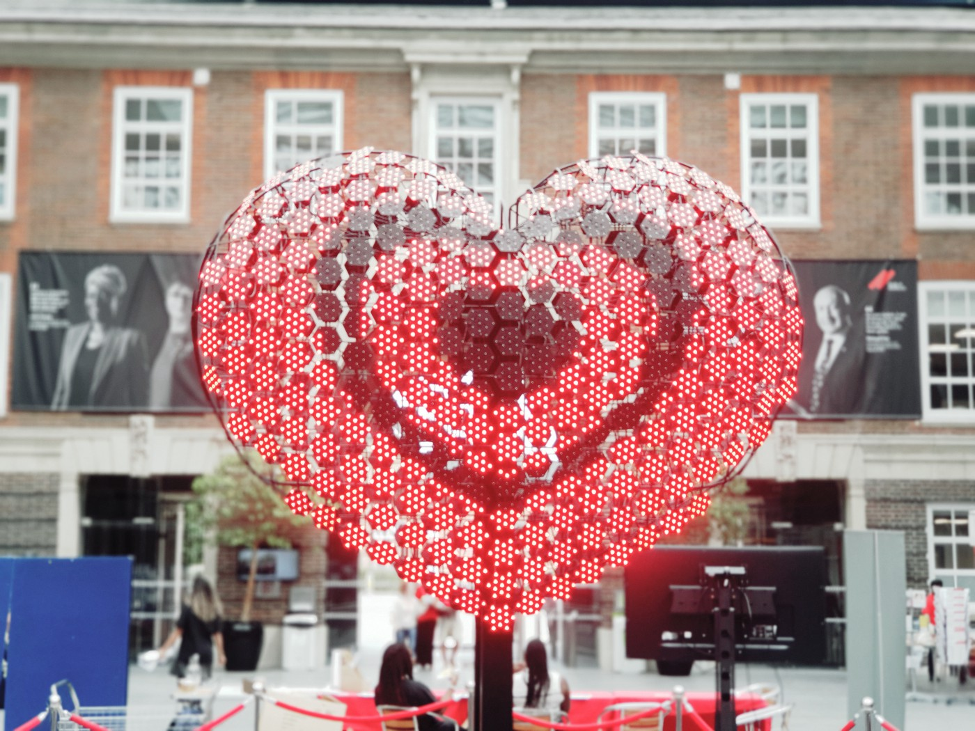 A large set of led lights shaped into a red heart in a university quad