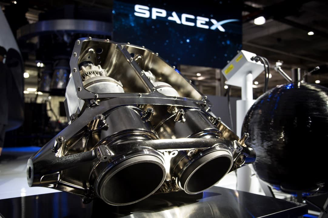 A small SpaceX SuperDraco rocket engine with two nozzles on a table.