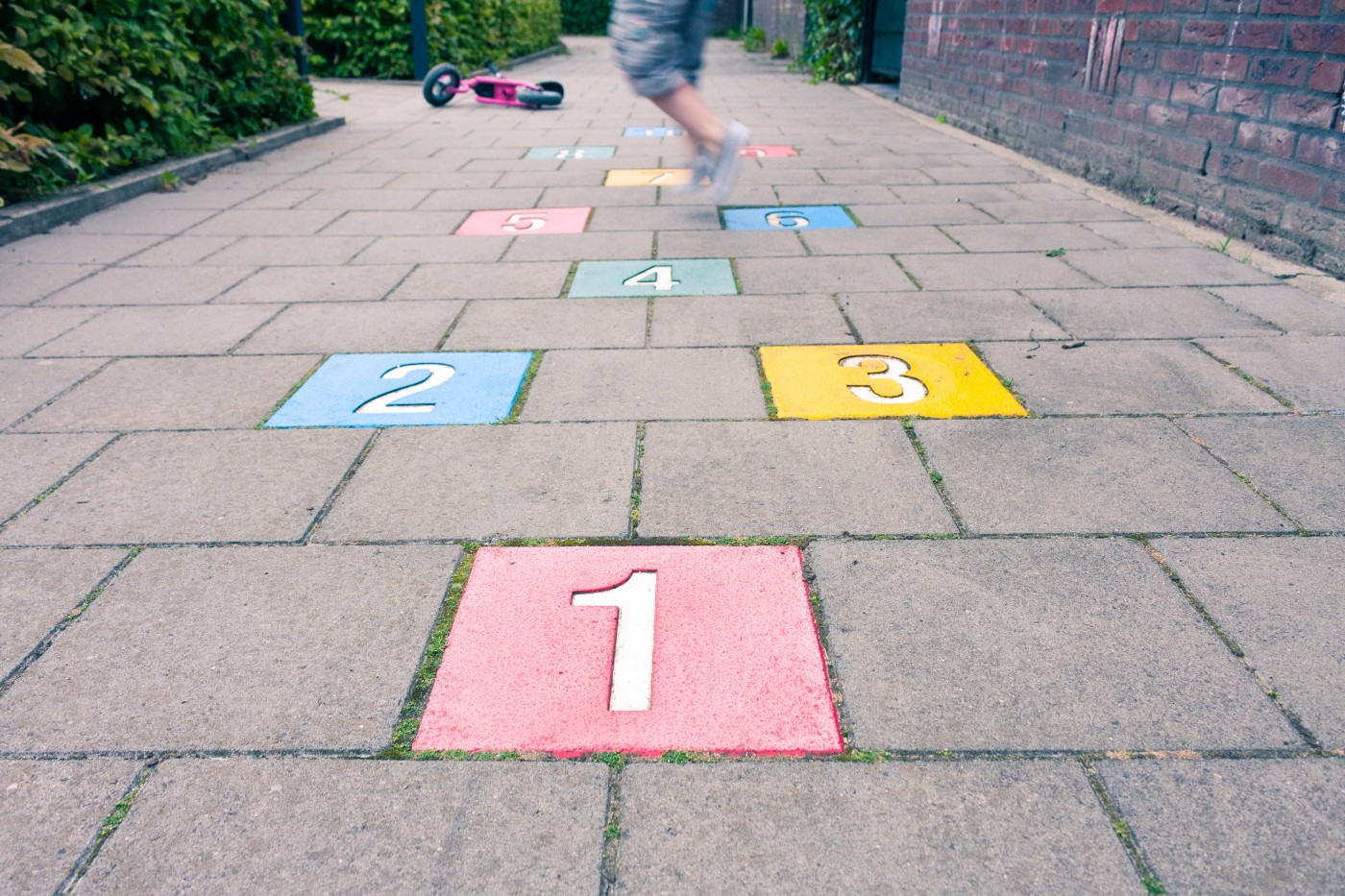 Colorful hopscotch numbers 1 to 3 painted into squares of a concrete footpath