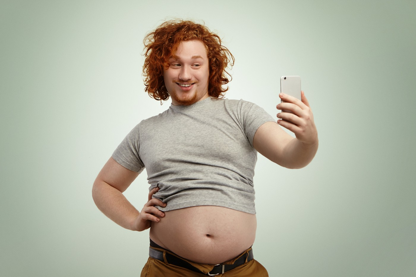 obese-young-male-with-curly-ginger-hair-beard-holding-mobile-phone-posing-selfie-looking-with-flirty-smile-while-his-fat-belly-hanging-out-grey-shrunk-t-shirt-jeans-pants—Un Swede