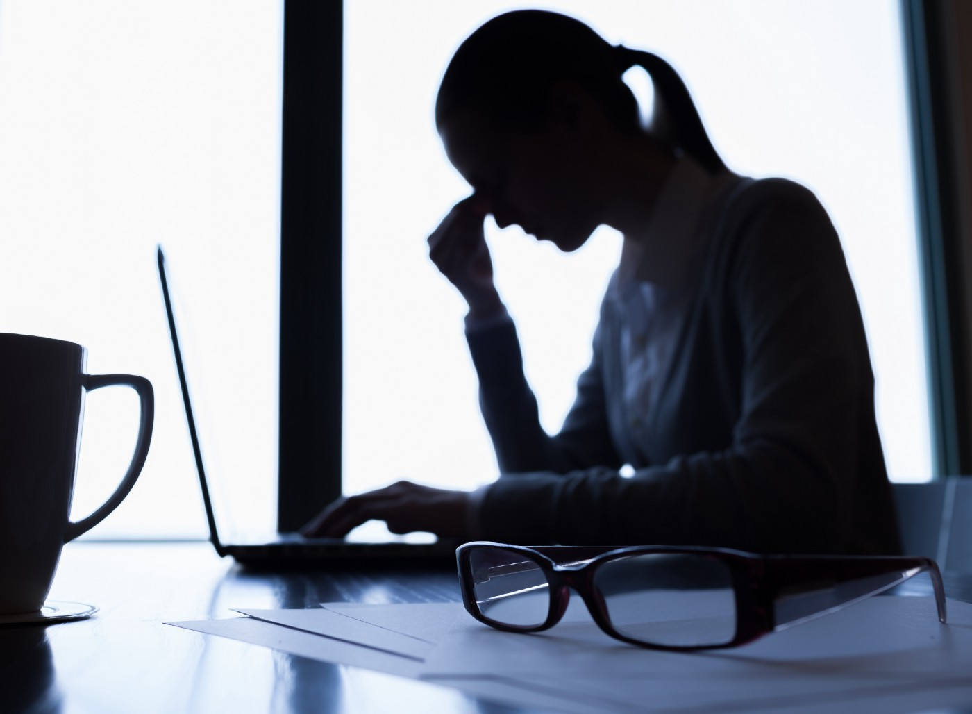 Image of sad, depressed woman at her desk, laptop open with coffee cup and reading glasses in foreground.