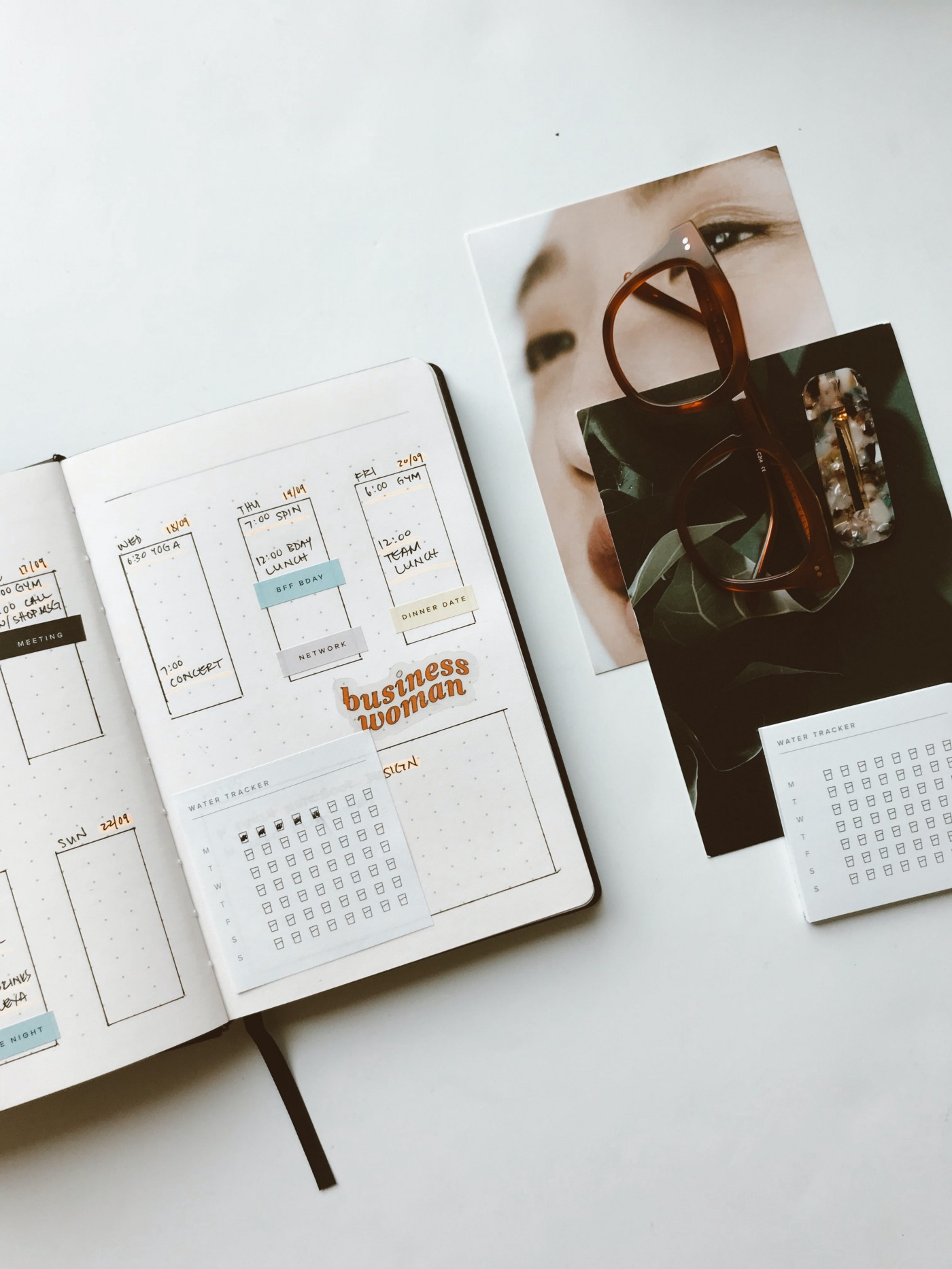 Image of an open planner, calendar, glasses & workspace.