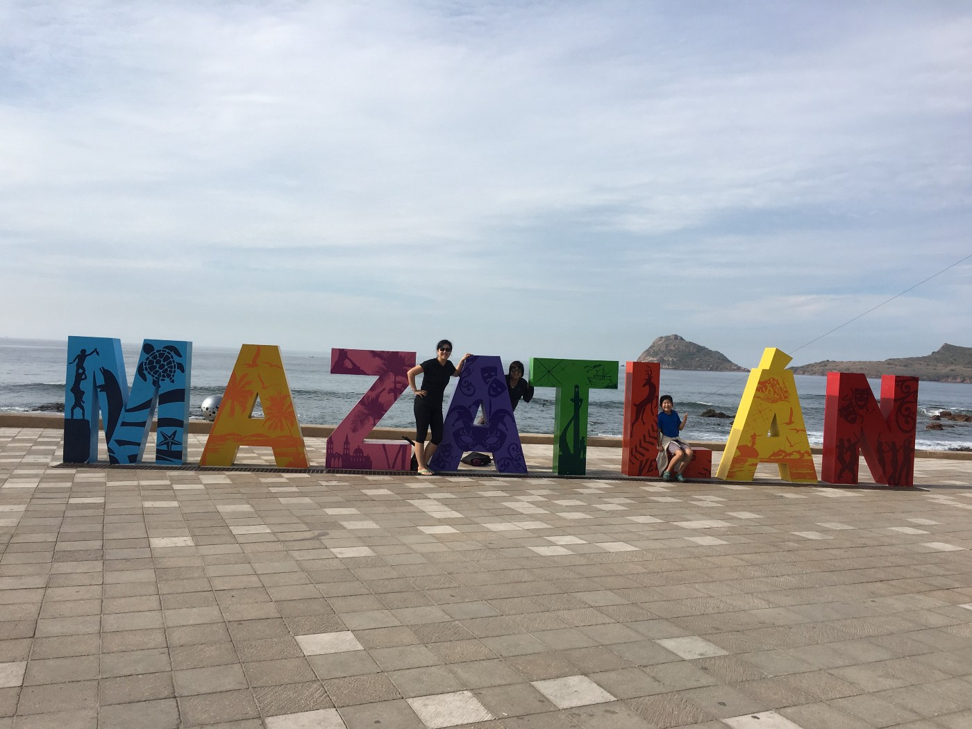Three people pose next to the large letters (each about 5' tall) spelling out Mazatlan