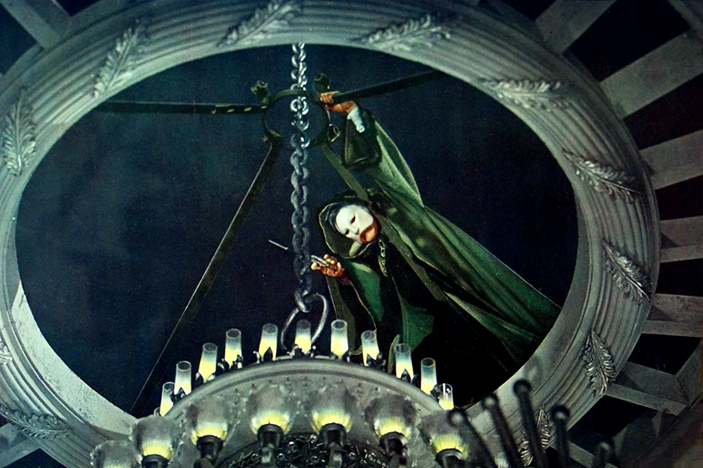 Film still from 1943's Phantom of the Opera where masked title character is in opening above chandelier, sawing its chain.