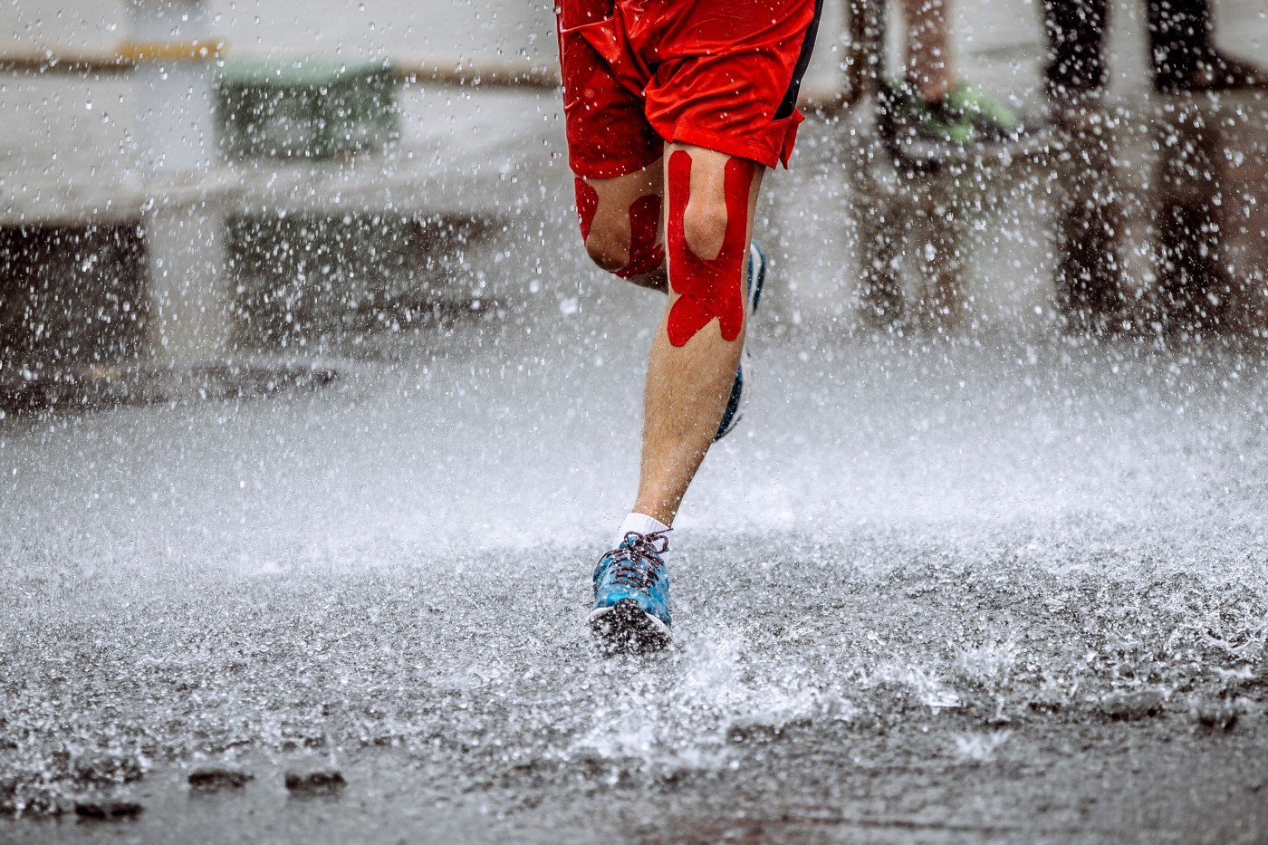 picture of runners legs, splashing on a wet road