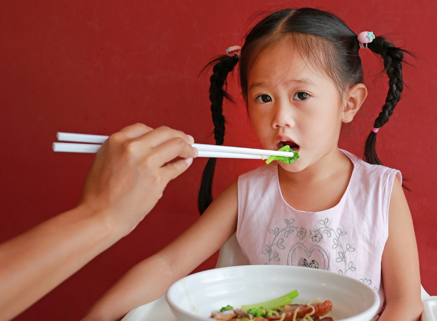 mother-feeding-vegetable-her-daughter-high-chair-against-red-wall-background—Un Swede