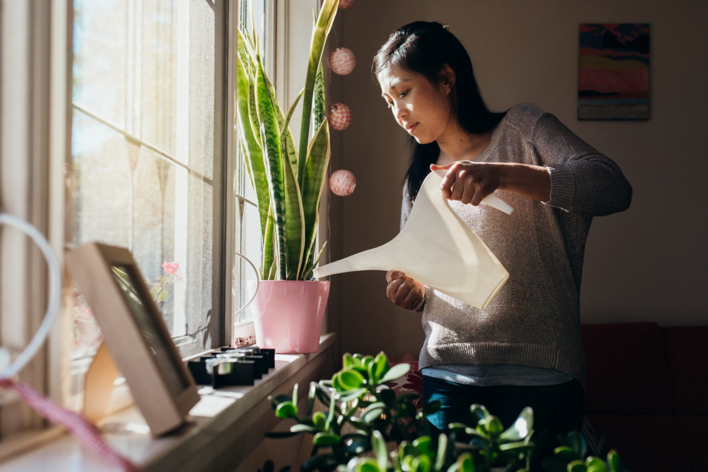 A photo of an Asian woman watering plants on her windowsill at home.