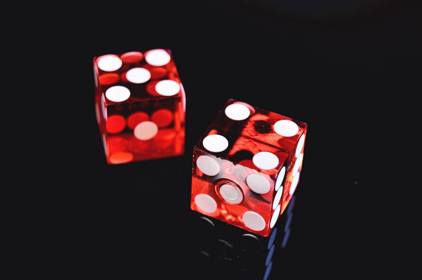 Two red die on a black background