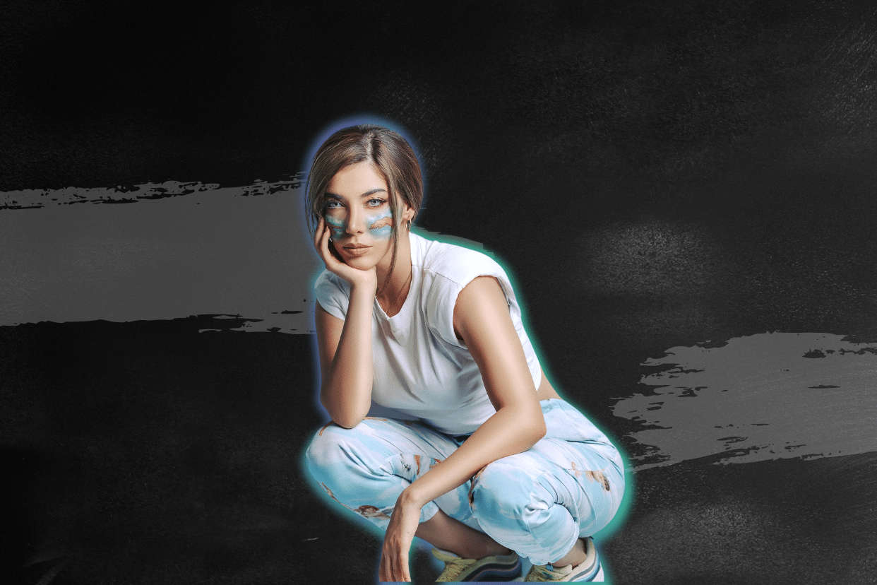A picture of a young woman with paint on her face squatting and smiling.