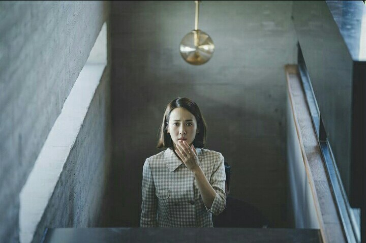 A still of a shocked female character from the movie 'Parasite' directed by Bong Joon-ho and released in 2019.