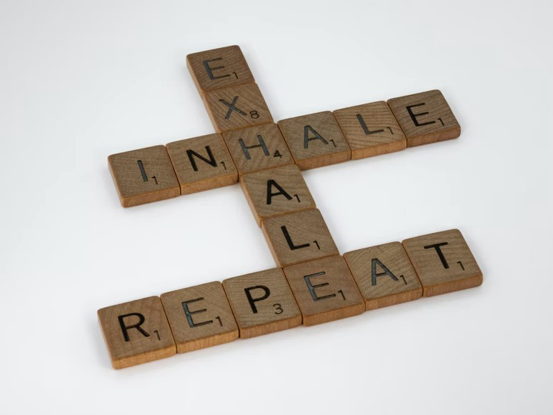 Inhale, Exhale, Repeat spelled out in scrabble letters—meditate
