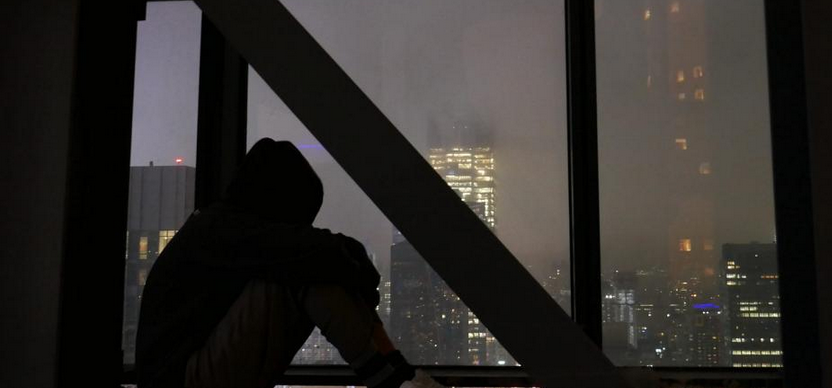 a hooded figure looks out a window at the New York night sky