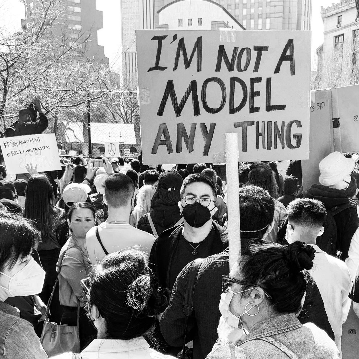 """black and white photo of the crowd at a rally to Stop Asian Hate in Columbus Park, Chinatown, NYC; Bowen Yang stands underneath a protest sign that reads """"I'm not a model anything."""""""