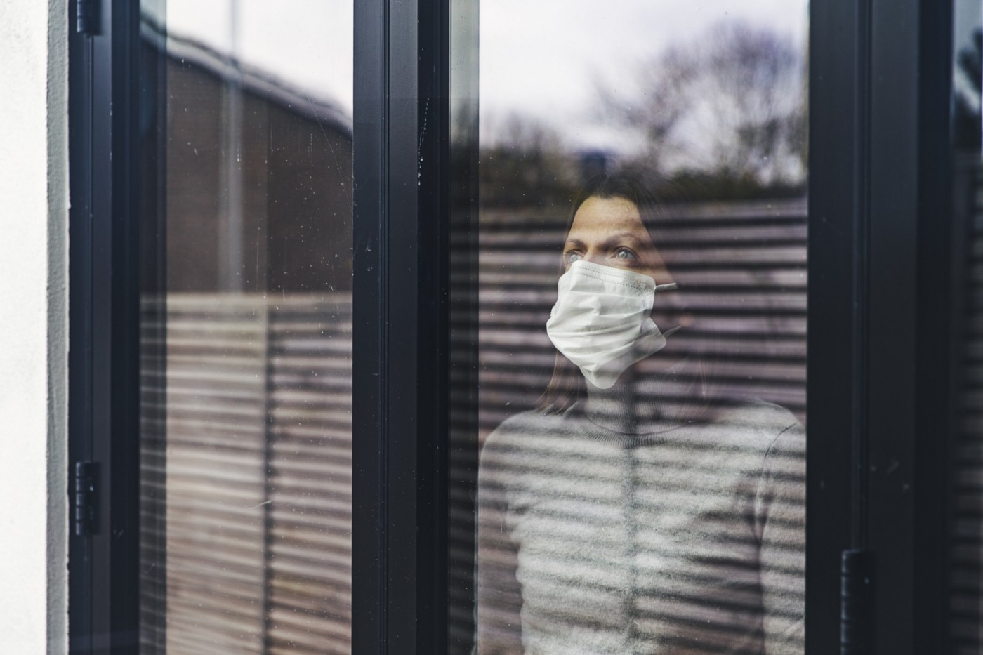 A photo of a woman wearing a mask looking out the window from her home.