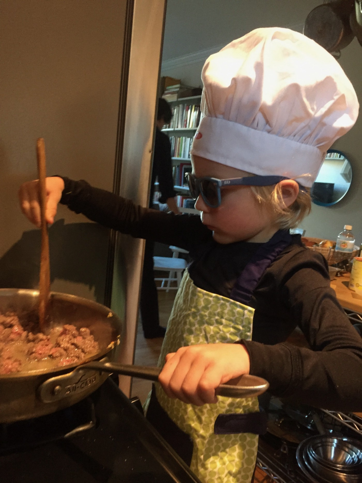 A kid with a chef's hat, stirring something in a pot.
